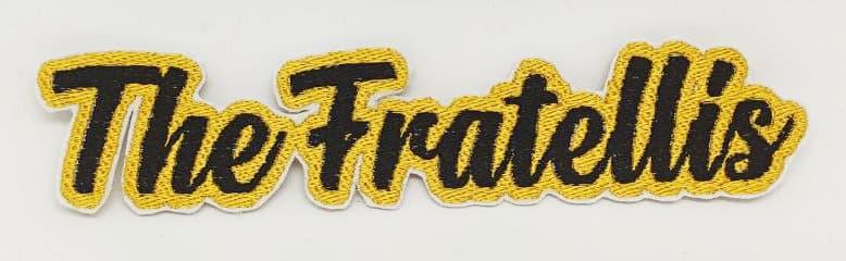 Toppa ricamata scritta corsivo nera contorno oro The Fratellis su sfondo bianco
