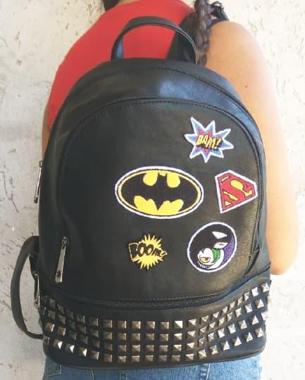 Fotografia ragazza di spalle con zaino di pelle nero con borchie con diverse toppe a tema fumetto e Batman