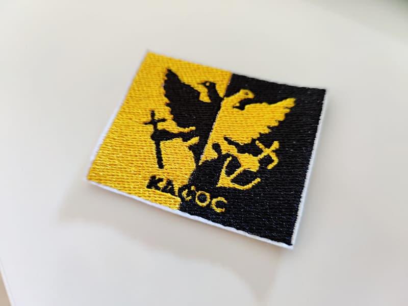 Fotografia di una toppa di una bandiera metà gialla e metà nera con al centro un'aquila che regge con una zampa una spada e con l'altra regge un'ancora e con scritta Kagog in basso