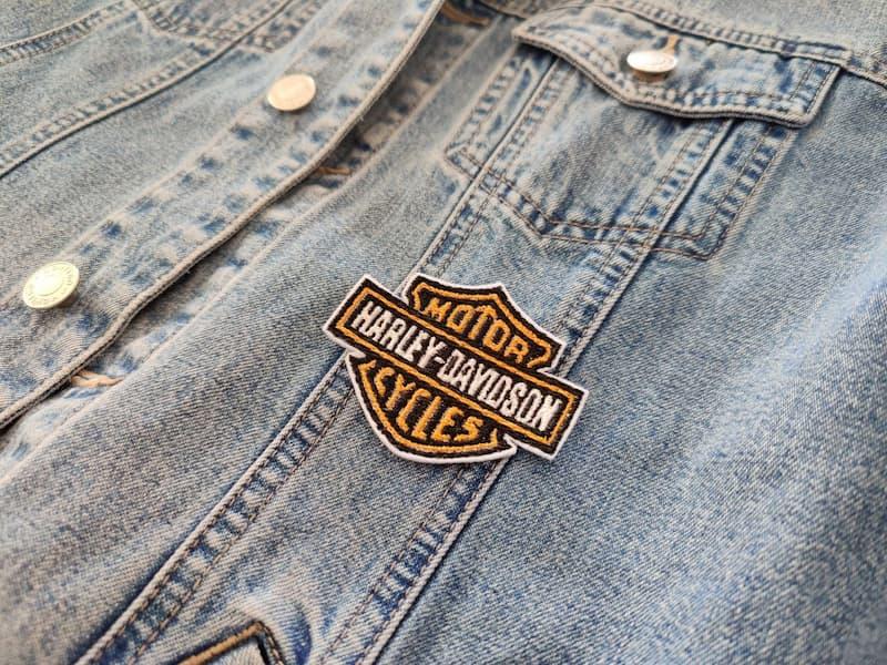 Fotografia di un dettaglio di un giubbotto di jeans con toppa a forma del logo Harley-Davidson Motorcycles arancione bianca e nera