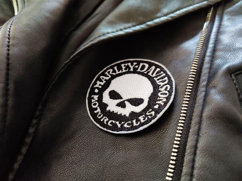Fotografia di un dettaglio di un giubbotto di pelle nero con toppa rotonda nera con teschio e scritta Harley-Davidson Motorcycles