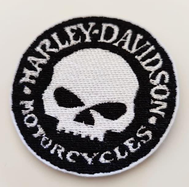 Fotografia toppa rotonda nera con testa teschio al centro e scritta sul contorno in stampatello bianco Harley-Davidson Motorcycles